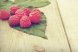 Fresh ripe raspberries with leaf on wooden table