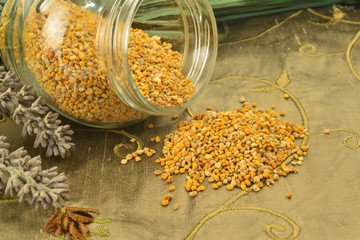 Bee pollen in glass jar and flowers