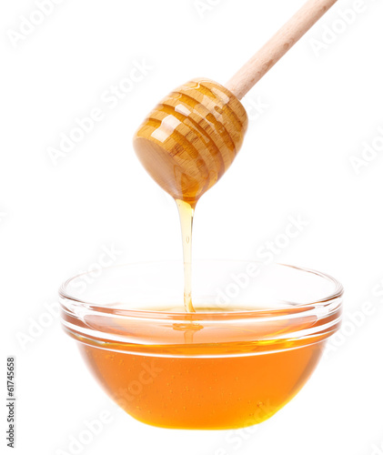 Bow of honey and wooden spoon.