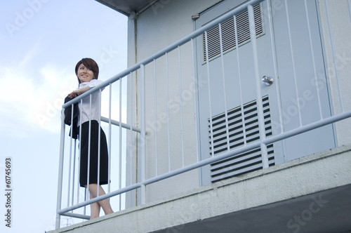 Japanese woman in her twenties looking outside from the landing