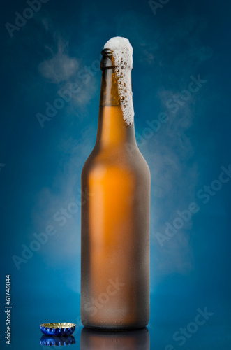 Beer frothing out of brown bottle