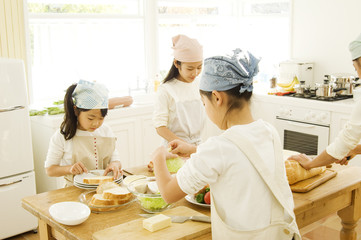 Four Japanese daughters cooking in kitchen