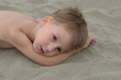 thougtful little boy lying on the sand