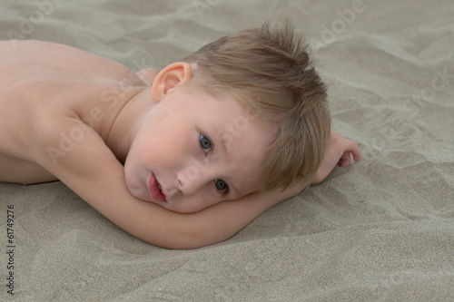 thougtful little boy lying on the sand