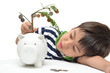 Little boy saving money in piggy bank money growing up as tree