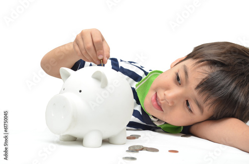 Little boy saving money in piggy bank