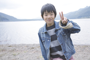 boy posing with peace sign by lakeside