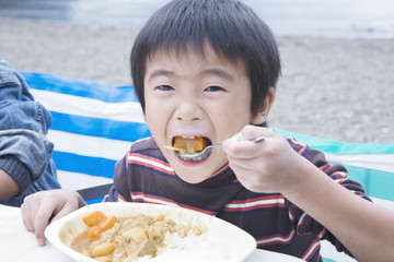 boy eating curry and rice outdoors