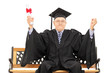 Mature man celebrating his graduation seated on wooden bench