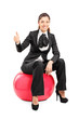 Young businesswoman sitting on pilates ball and giving thumb up
