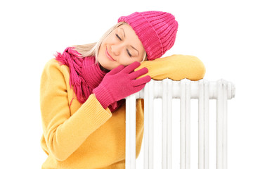 Young female in winter clothes resting on a radiator