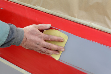Painting, car ready for repaint, worker sanding primer