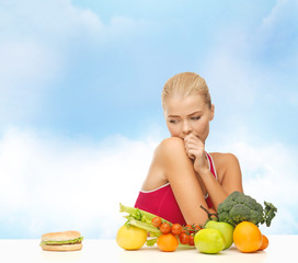 doubting woman with fruits and hamburger