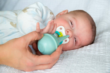Mother using bulb syringe to clean baby's nose