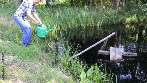 Young farm worker girl with watering-can draw water from pond