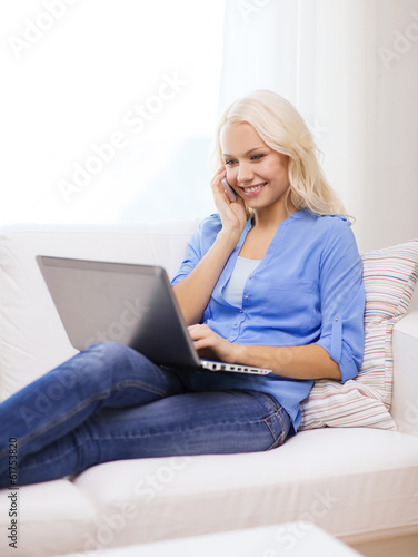 smiling woman with smartphone and laptop at home