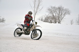 Motocross on snow, the driver manages motorcycle one arm on snow