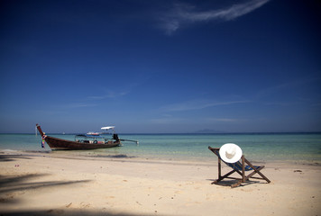 Beach chair with white hat on beautiful beach in Thailand