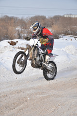 Motocross rider on a motorcycle driving on winter road holding u