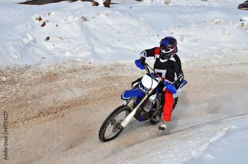 Motocross on snow racer on a motorcycle in the left turn having