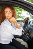 Beautiful smiling middle-aged redhead woman in a car