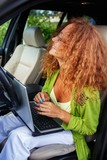 Beautiful middle-aged redhead woman with laptop in a car