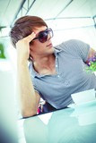 Handsome young man in sunglasses sitting on summer terrace