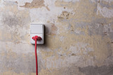Socket with red wire on grungy wall
