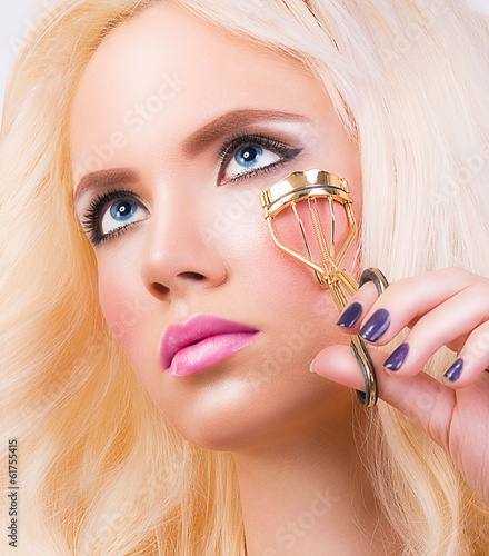 Beautiful young woman with eyelash curler
