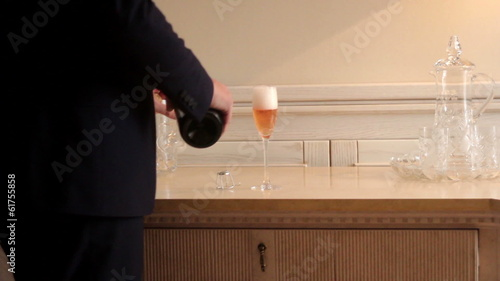 groom pouring champagne into glasses