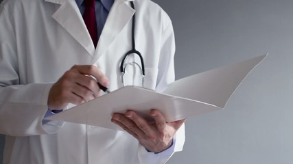 Male doctor writing prescription while standing.