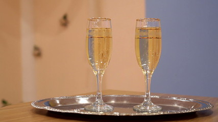 two glasses with champagne standing on the table