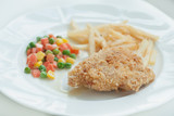 A chicken fried steak with french fries and vegetables
