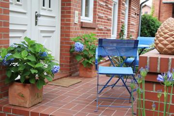 Backsteinhaus mit blauen Gartenmöbeln und Hortensien
