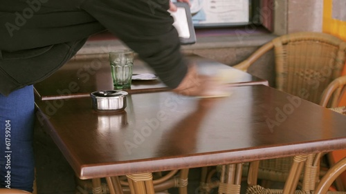 Waiter cleaning a table at restaurant
