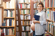Young pregnant woman holding book in library