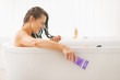 Happy young woman with hair conditioner in bathtub