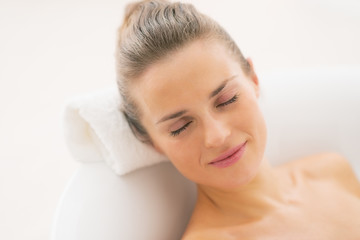 Happy young woman relaxing in bathtub