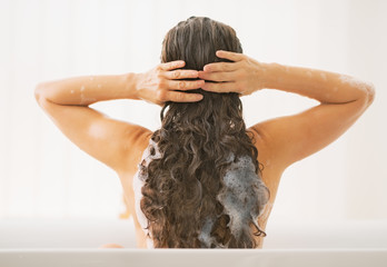 Young woman washing hair. rear view