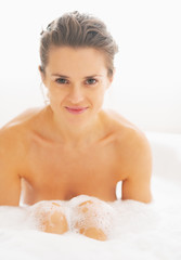 Portrait of happy young woman sitting in bathtub
