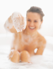 Closeup on happy young woman playing with foam in bathtub