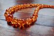 Leinwandbild Motiv Amber necklace on dark wood
