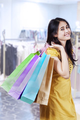Happy shopaholic holding shopping bags