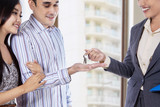 Real estate agent handing over keys of new house to young couple