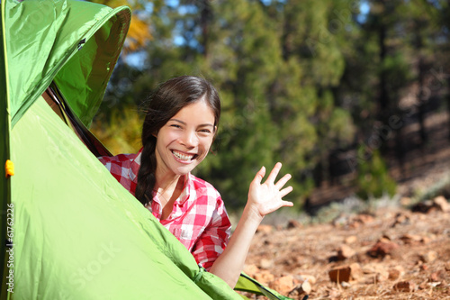 Camping woman waving hello from tent