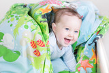 Funny baby playing in a bed under a blue blanket