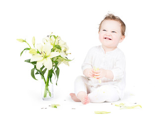 Funny little baby playing with lily flowers, on white