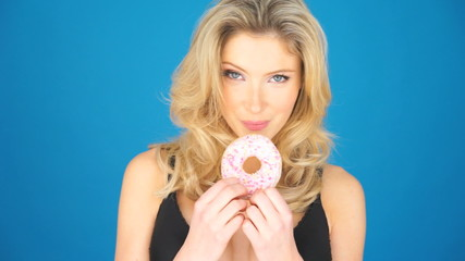 Beautiful blond woman eating a big doughnut