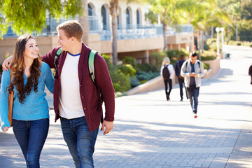 Student Couple Walking Outdoors On University Campus