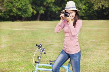 female photographer holding camera and sitting bike
